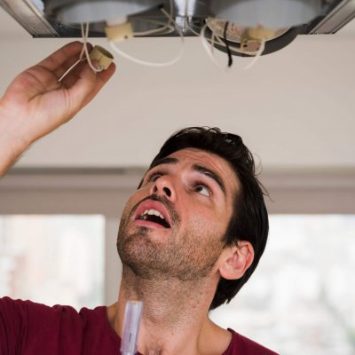 close-up-of-male-electrician-installing-holder-of-ceiling-light